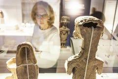 Ältere Frau, Carthaginian Göttinfigürchen beobachtend Stockfotografie