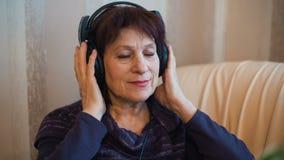 Ältere Frau in den Kopfhörern stock footage
