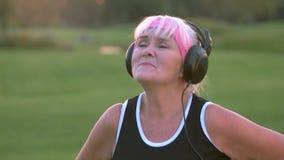 Ältere Frau in den Kopfhörern singend stock footage