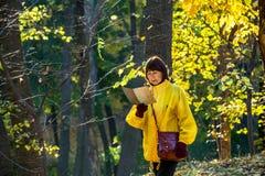 Ältere Frau in der gelben Jacke alte Karte im Wald lesend Lizenzfreie Stockfotos