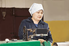 Ältere Frau an der grünen Maschine stockfotografie
