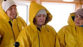 Ältere Frau der Gruppe in der gelben wasserdichten Jacke auf Passagierschiffsbrett Reife Frauen in der schützenden Jackenweileret stock footage