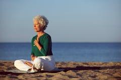 Ältere Frau in der Meditation durch Ozean lizenzfreie stockfotos