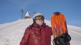 Ältere Frau in der roten Jacke hält Skateboard auf schneebedecktem Hügel stock video