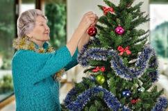 Ältere Frau in der Türkisstrickjacke Weihnachtsbaum verzierend Lizenzfreies Stockbild