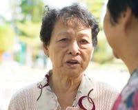 Ältere Frau der Traurigkeit, die traurige Geschichte erzählt Stockfotografie