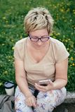 Ältere Frau in der zufälligen Ausstattung, sitzend auf dem Gras im Park Lizenzfreie Stockbilder
