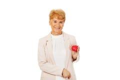 Ältere Frau des Lächelns, die Herzmodell hält Stockfotografie