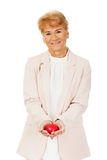 Ältere Frau des Lächelns, die Herzmodell hält Lizenzfreies Stockbild