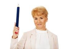 Ältere Frau des Lächelns, die oben mit hege Stift zeigt Stockfotos