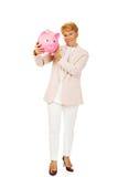 Ältere Frau des Lächelns, die Sparschwein hält Stockbilder
