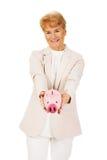 Ältere Frau des Lächelns, die Sparschwein hält Stockbild