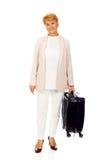 Ältere Frau des Lächelns mit Koffer Stockfotografie