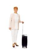 Ältere Frau des Lächelns mit Koffer Stockfoto