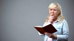 Ältere Frau, die über Informationen vom Buch, lebenslange Selbstausbildung denkt lizenzfreie stockbilder