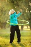 Ältere Frau, die Übungen in der Natur tut Stockbild