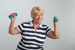 Ältere Frau, die Übungen mit Dummköpfen tut Lizenzfreie Stockbilder