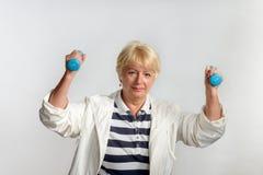 Ältere Frau, die Übungen mit Dummköpfen tut Lizenzfreies Stockfoto