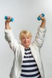 Ältere Frau, die Übungen mit Dummköpfen tut Stockfotos