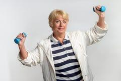 Ältere Frau, die Übungen mit Dummköpfen tut Stockbild