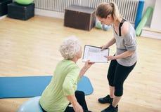 Ältere Frau, die Übungsplan mit persönlichem Trainer betrachtet lizenzfreies stockbild