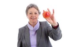 Ältere Frau, die Apfel - ältere Frau auf weißem Hintergrund hält Lizenzfreies Stockbild