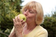 Ältere Frau, die Apfel genießt Stockfoto