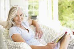 Ältere Frau, die außerhalb der Lesezeitschrift sitzt Stockfoto