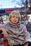 Ältere Frau, die auf Bank nach dem Einkauf im Mall sich entspannt Lizenzfreies Stockfoto