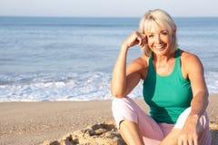 Ältere Frau, die auf dem entspannenden Strand sitzt Lizenzfreie Stockfotografie