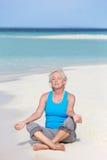 Ältere Frau, die auf schönem Strand meditiert Lizenzfreie Stockbilder
