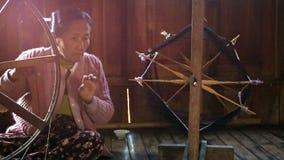 Ältere Frau, die auf die traditionelle Art spinnt Stockfoto
