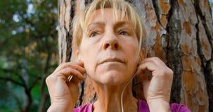 Ältere Frau, die auf einem Baum und einer hörenden Musik 4k sich lehnt stock video