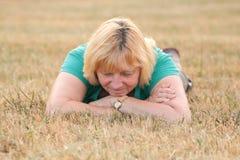 Ältere Frau, die auf Gras liegt Lizenzfreie Stockfotografie