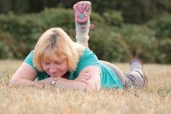 Ältere Frau, die auf Gras mit einem Bein oben liegt Stockfotografie