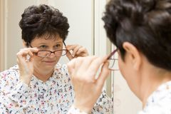 Ältere Frau, die auf neuen Brillen versucht und über den Gläsern im Spiegel schaut Lizenzfreie Stockbilder