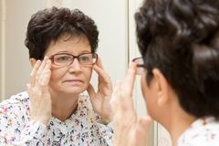 Ältere Frau, die auf neuen Gläsern versucht und im Spiegel schaut Lizenzfreies Stockfoto