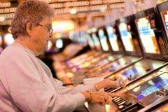 Ältere Frau, die auf Spielautomaten spielt lizenzfreie stockfotos