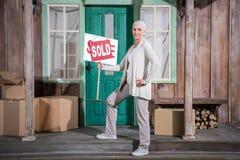 Ältere Frau, die auf Treppe des neuen Hauses steht und Verkaufszeichen hält Stockfotos