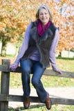 Ältere Frau, die auf Zaun sitzt Stockbilder