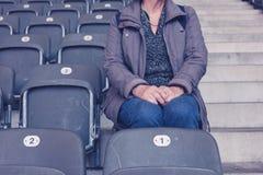 Ältere Frau, die auf Zuschauertribünen im leeren Stadion sitzt Stockbild