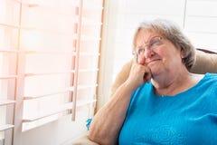 Ältere Frau, die aus ihrem Fenster heraus anstarrt Stockfotografie