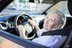 Ältere Frau, die Auto am sonnigen Tag fährt lizenzfreies stockfoto