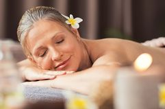 Ältere Frau, die am Badekurort sich entspannt Stockfoto