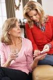 Ältere Frau, die bei der Medikation geholfen wird Lizenzfreie Stockbilder