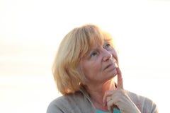Ältere Frau, die bei Sonnenuntergang denkt Stockfoto