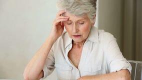 Ältere Frau, die bei Tisch sitzt, Rechnungen ausarbeitend stock footage