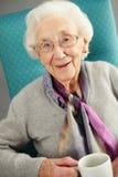 Ältere Frau, die bequemen trinkenden Tee schaut lizenzfreies stockfoto