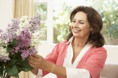 Ältere Frau, die Blumen anordnet Stockbild