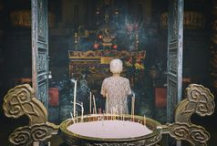 Ältere Frau, die Buddha am Tempel betet stockbilder